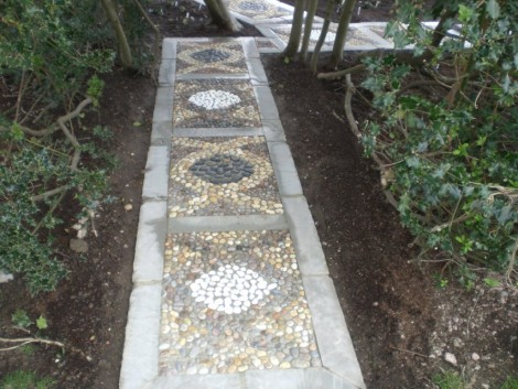 Tumbled Kandla Grey stones bordering a mix of pebbles inset in cement to make a feature path